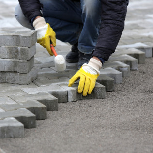 A landscaper installing pavers in Olive Branch, MS